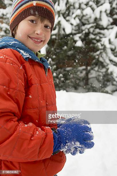 Boy packing snow ball