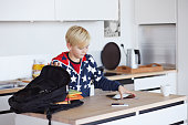 Boy packing tablet and book in schoolbag