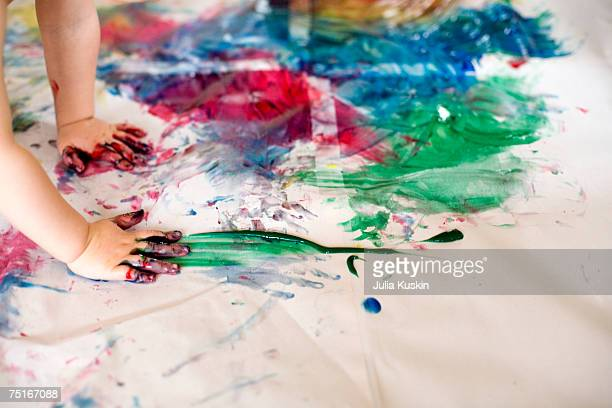 Boy (2-3) painting by hands