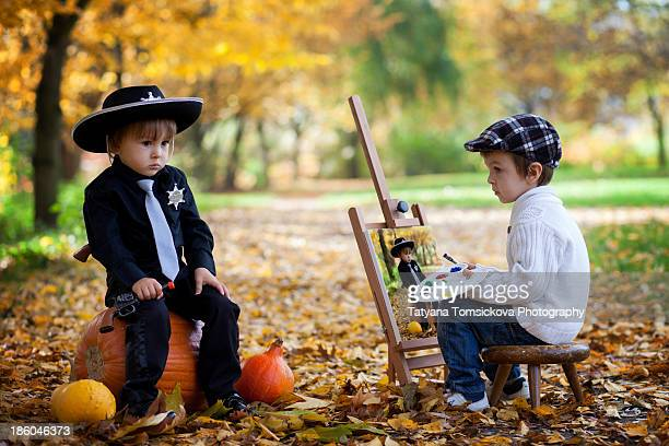 Boy, painting other boy, dressed for halloween