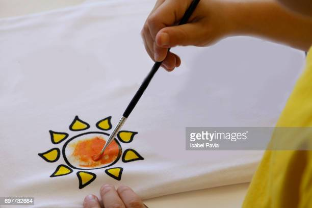 Boy painting the sun with watercolors