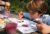 Boy painting with water colour
