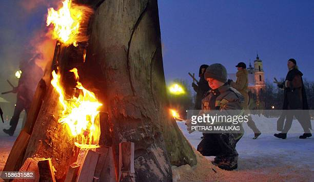 A boy participates in winter solstice celebrations to complete the Christmas 'Blukis' burning ceremony at Lukiskes Square in Vilnius on December 21...