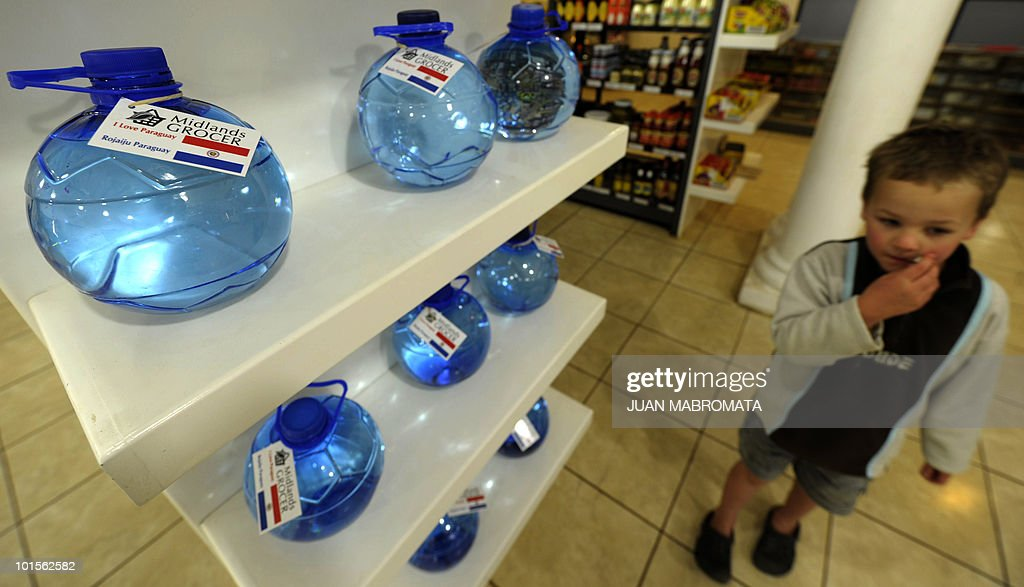 A boy passes by a gondola that offers mineral water bottles shaped like football with Paraguay's national flags at a grocery store near Paraguay's squad base camp in Balgowan, some 400 km at south-east of Johannesburg, on June 2, 2010. Paraguay will take part in the FIFA 2010 World Cup hosted in South Africa from June 11 to July 11.