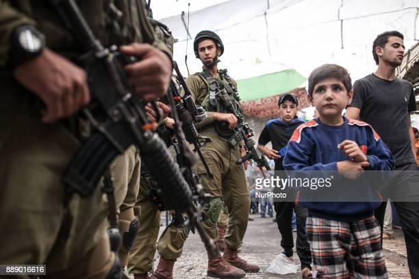 Boy passing Israeli IDF soldiers in Palestinian part of Hebron In 2014 Israel launched military operation on 8 July 2014 in the Hamasruled Gaza Strip...