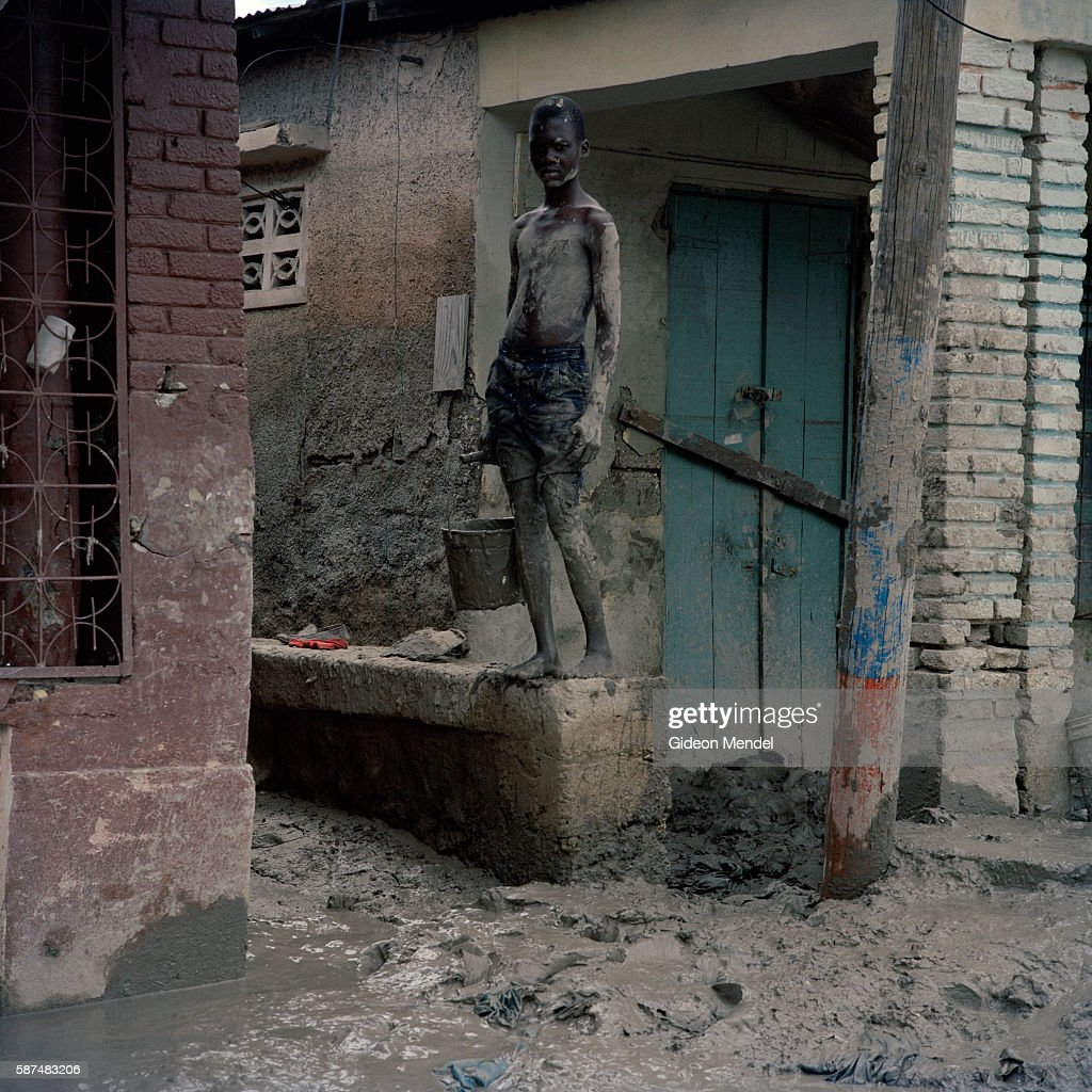 A boy pauses for a moment as works on cleaning the mud out of his flooded home in the city of Gonaives two weeks after it was flooded during...