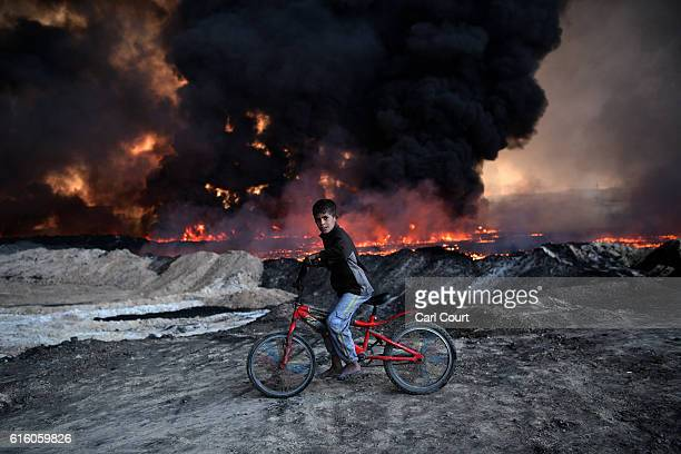 A boy pauses on his bike as he passes an oil field that was set on fire by retreating ISIS fighters ahead of the Mosul offensive on October 21 2016...
