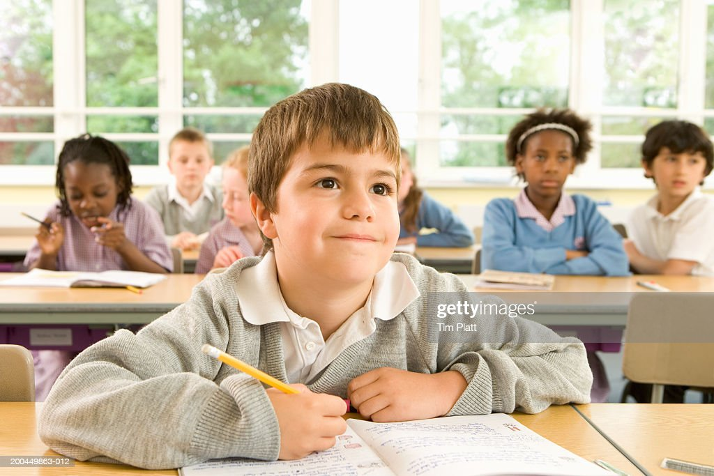 Boy Paying Attention In Class Other Children In Background ...