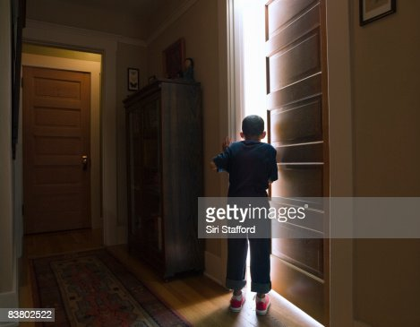 Boy peeking into room with light coming out