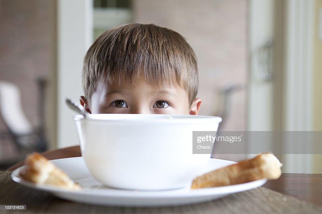 Boy peeking out over his bowl : Stock Photo