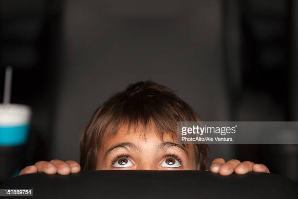 Boy peeking over top of seat during horror movie in theater