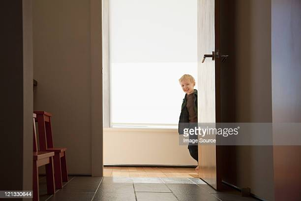 Boy peeking round doorway