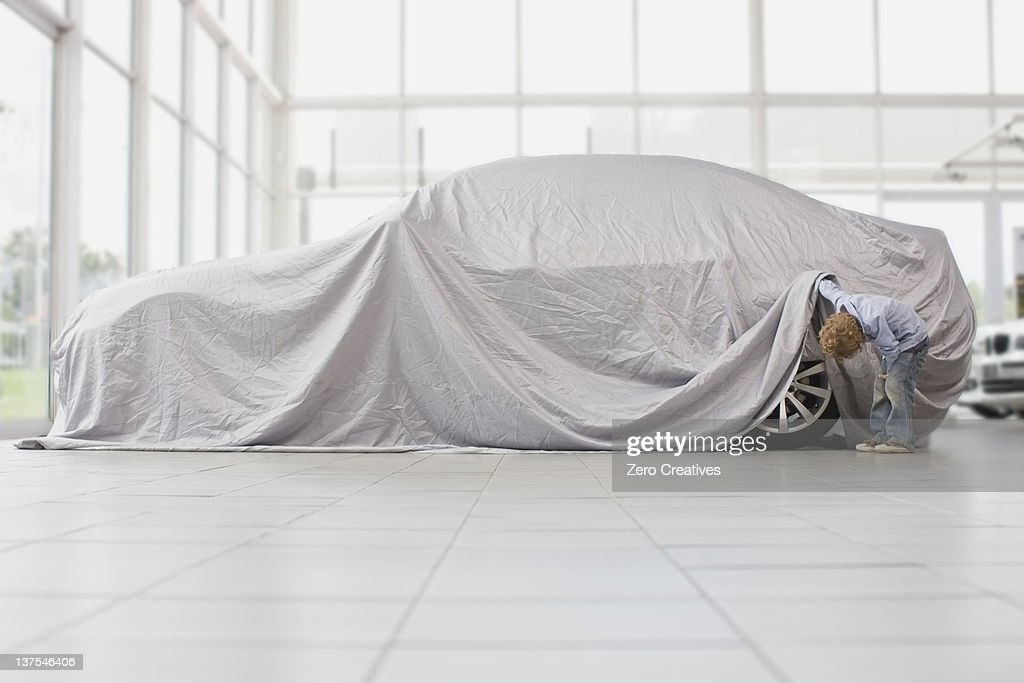 Boy peeking under cloth on car : Stock Photo