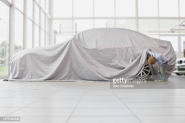 Boy peeking under cloth on car
