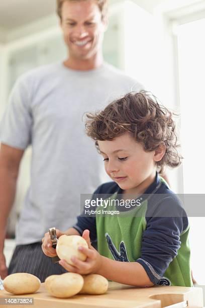 Boy peeling potatoes in kitchen