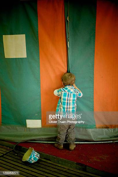 Boy peeping through circus tent
