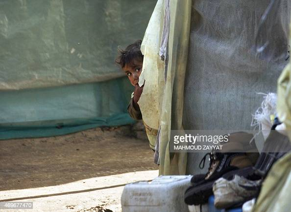 A boy peeps from behind a tent at a UNHCR's camp for Syrian refugees in south Lebanon on April 14 2015 International donors pledged $38 billion to...