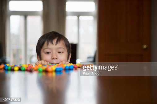 Boy peering over table at candy : Stock Photo