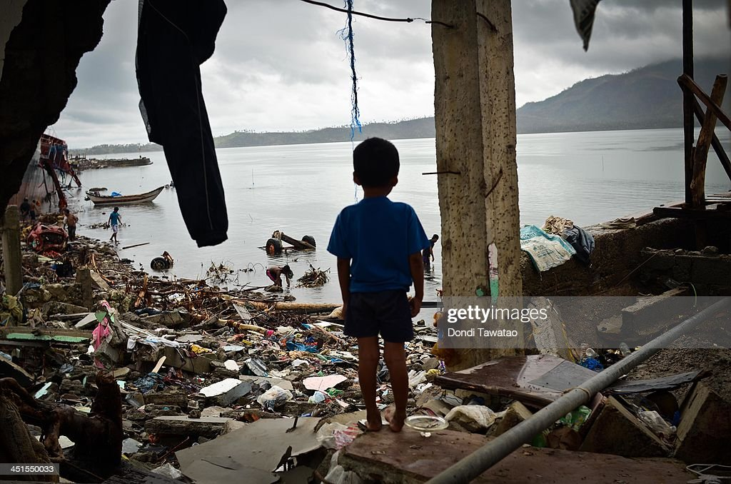 TACLOBAN, LEYTE, PHILIPPINES - NOVEMBER 23: A boy peers out of a damaged structure near the shoreline on November 23, 2013 in Tacloban, Leyte, Philippines. Bodies continue to be recovered nearly two weeks after the devastating Typhoon Haiyan hit as the official death toll now exceeds 5,000. The typhoon has been described as one of the most powerful to ever to hit land, leaving thousands dead and hundreds of thousands homeless. Countries all over the world have pledged relief aid to help support those affected by the typhoon, but damage to the airport and roads have made moving the aid into the most affected areas very difficult.