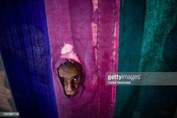 A boy peers through a food tent whilst awaiting a handout meal before 'Iftar' when Muslims break their fast on the second day of the holy month of...