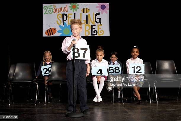 Boy (8-9) performing at spelling bee competition