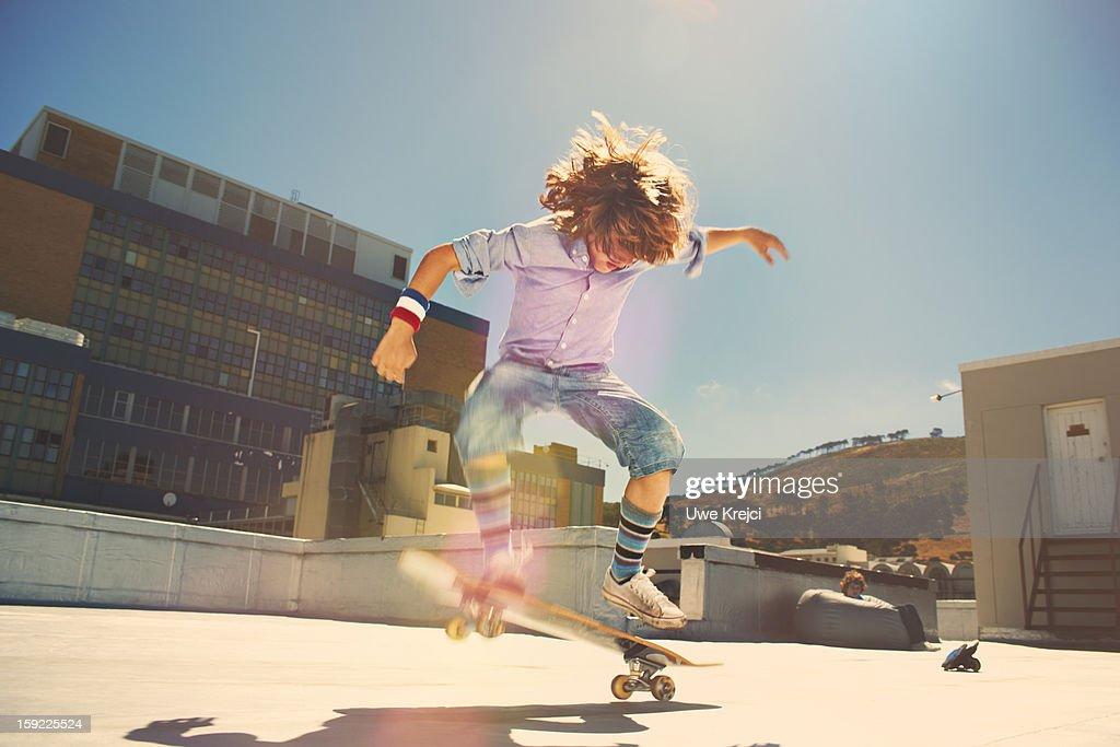 Boy performing jump on skateboard : Stock Photo