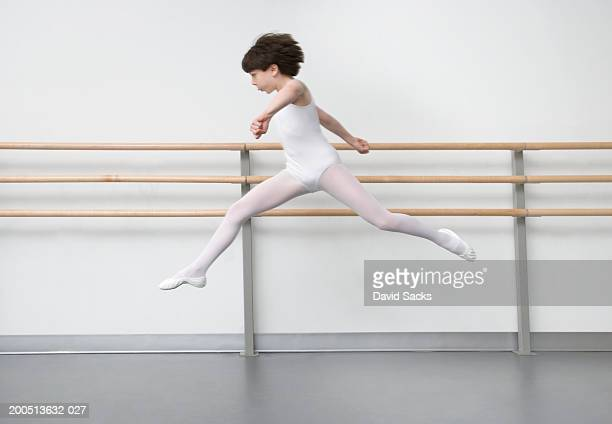 Boy (9-13) performing leap in ballet class
