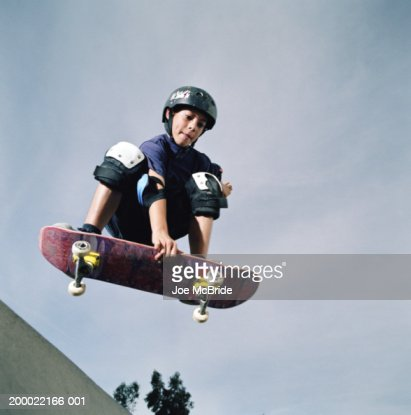 Boy (9-11) performing mid-air jump on skateboard, low angle view