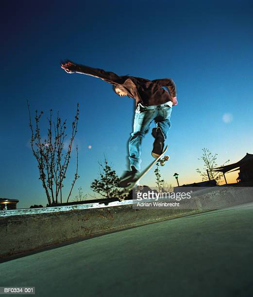 Boy (14-16) performing 'ollie' jump on skateboard, low angle view