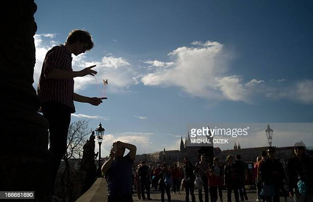 A boy performs with his YoYo on the Charles Bridge on April 15 2013 during a spring sunny day in Prague AFP PHOTO/MICHAL CIZEK