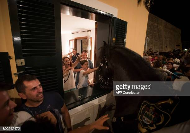 A boy pets a horse through the window of a house during the traditional San Juan festival in the town of Ciutadella on the Balearic Island of Menorca...