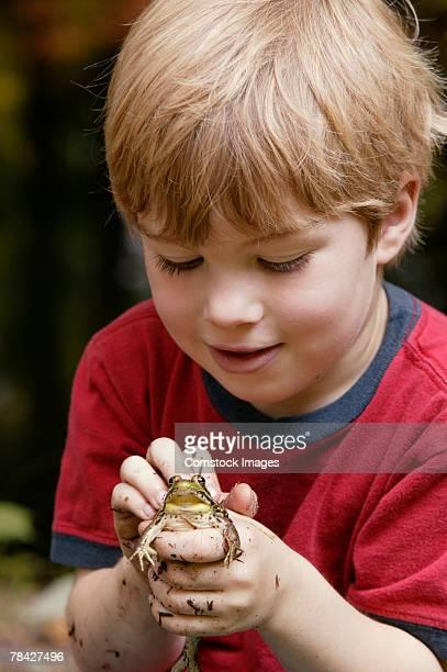 Boy petting frog