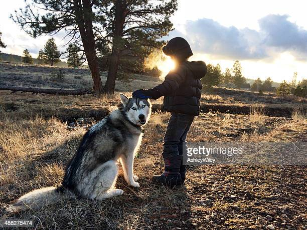 Boy petting his dog out in a wild field in autumn
