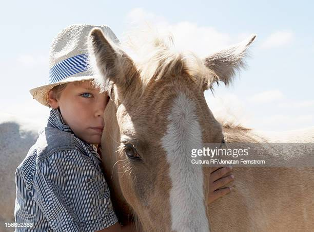 Boy petting horse outdoors