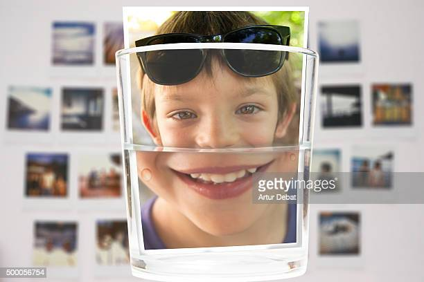 Boy photograph submerge in water with smiling face and sunglasses.
