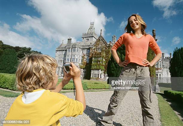 Boy (8-9) photographing girl (12-13) in front of castle