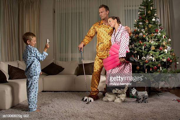 Boy (6-7) photographing parents near Christmas tree