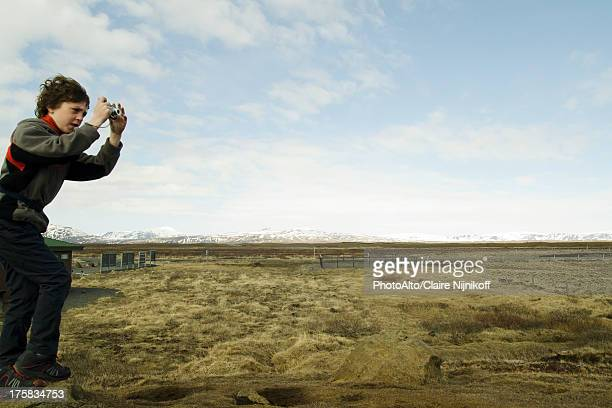 Boy photographing the Gullfoss landscape, Iceland