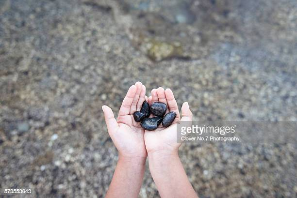 Boy picking up rocks in the sea.