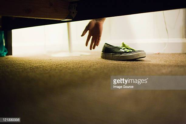 Boy picking up shoe from under bed