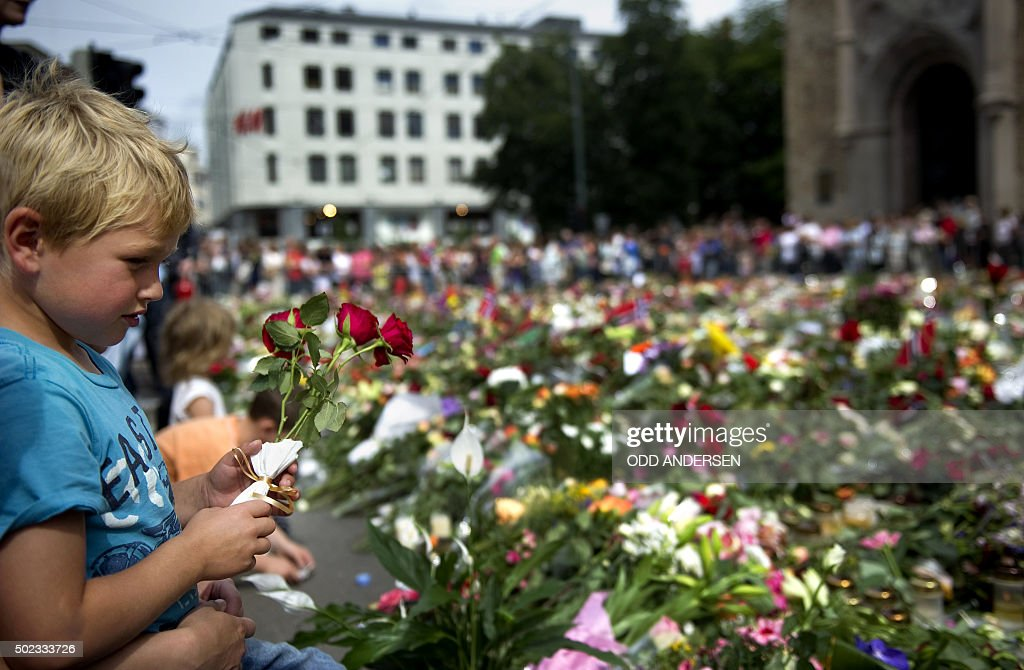 A boy places flowers at a makeshift memorial outside the Cathedral in Oslo on July 26 in honor of the victims of the July 22 twin attacks in downtown...