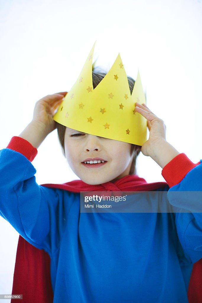 Boy placing crown on head : Stock Photo