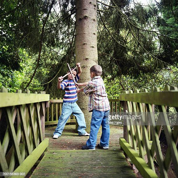 Boy (5-7) play fighting with sticks by tree
