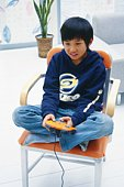 Boy playing a video game on a chair with his Legs Crossed, High Angle View