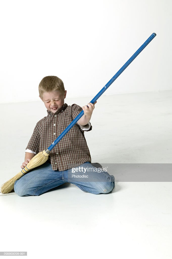 Boy (8-9) playing air guitar with broom in studio