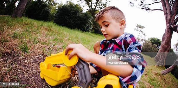 Boy playing and digging with toy excavator in garden