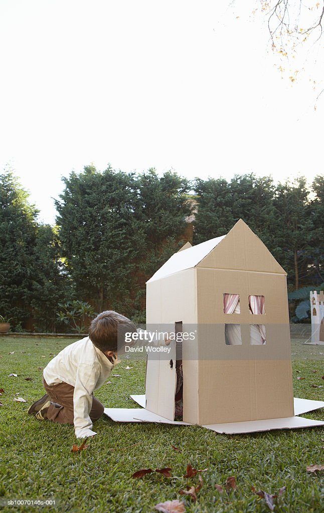 Boy (6-7) playing at cardboard house in garden