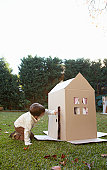 Boy (6-7) playing at cardboard house in garden