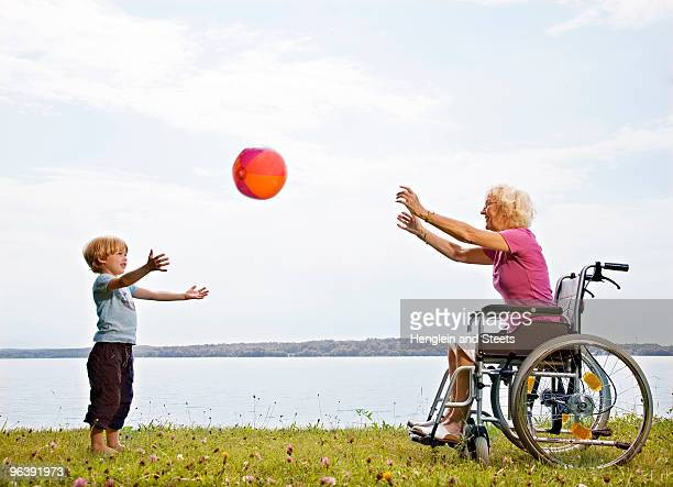 boy playing ball with senior woman