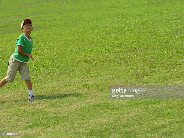 Boy playing catch in a field